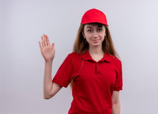 Zelfverzekerd jong leveringsmeisje in rood uniform die hallo gebaar op geïsoleerde witte ruimte doen