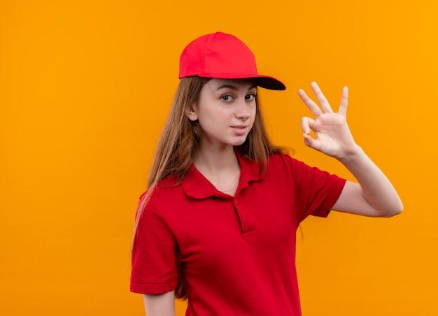 Zelfverzekerd jong leveringsmeisje in rood uniform doet ok teken op geïsoleerde oranje ruimte met exemplaarruimte