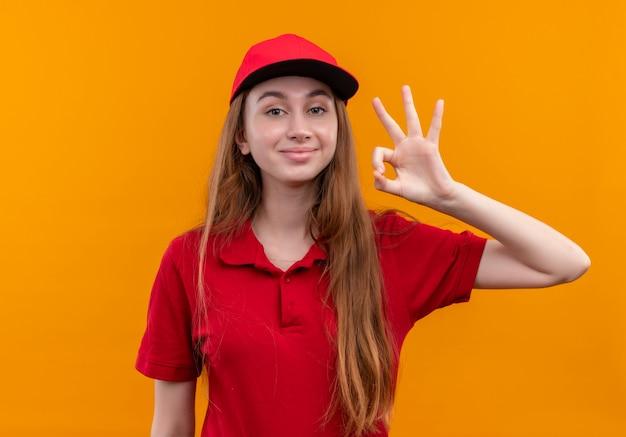 Zelfverzekerd jong leveringsmeisje in rood uniform doet ok teken op geïsoleerde oranje ruimte