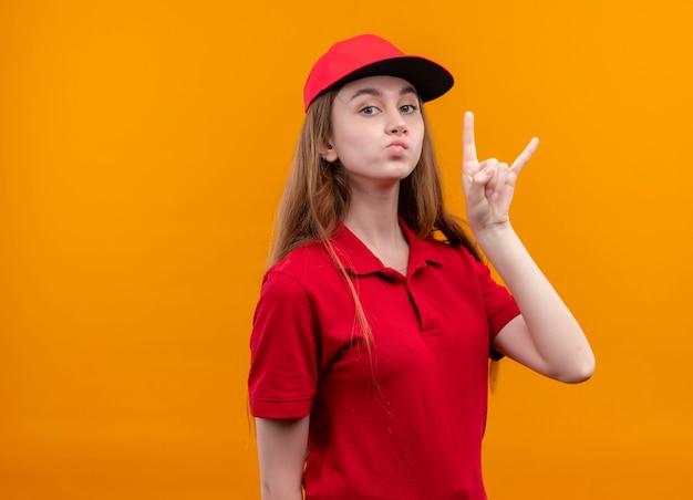 Zelfverzekerd jong leveringsmeisje in rood uniform doet rotsteken op geïsoleerde oranje ruimte met exemplaarruimte