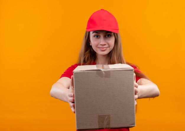 Zelfverzekerd jong leveringsmeisje in rood uniform uitrekkende doos op geïsoleerde oranje ruimte met exemplaarruimte