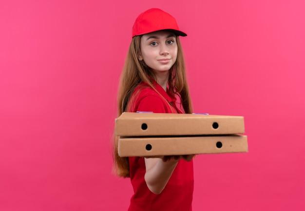 Zelfverzekerd jong leveringsmeisje in rood uniform uitrekkende pakket dat zich in profielmening op geïsoleerde roze ruimte met exemplaarruimte bevindt