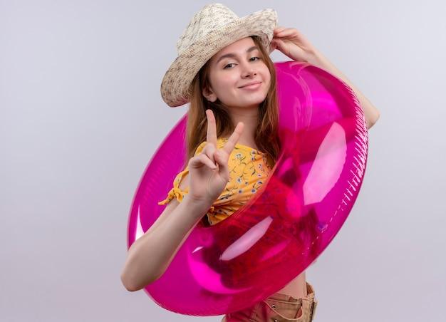 Zelfverzekerd jong meisje dat hoed draagt en zwemt ring die vredesteken doet en hand op hoed op geïsoleerde witte ruimte met exemplaarruimte zet