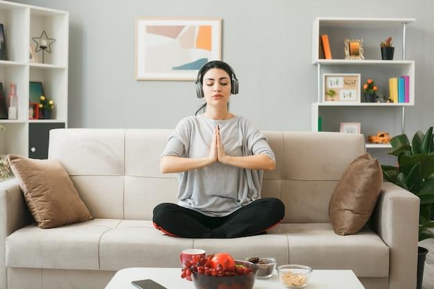 Zelfverzekerd jong meisje met een koptelefoon die yoga doet, zittend op de bank achter de salontafel in de woonkamer