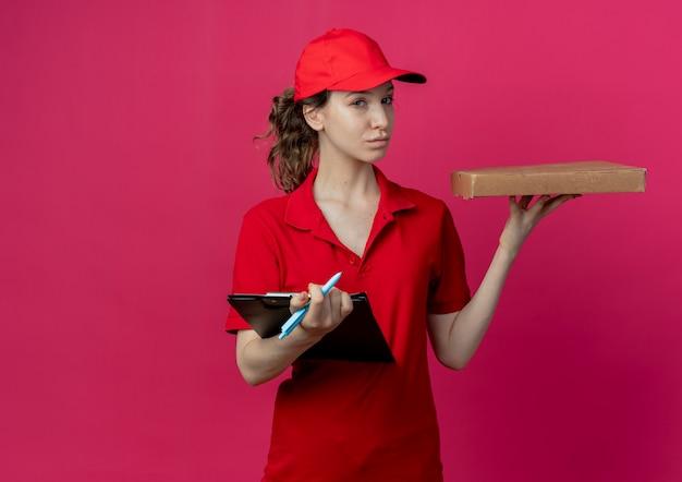 Zelfverzekerd jong mooi bezorgmeisje in rood uniform en pet met pizzapakketpen en klembord geïsoleerd op karmozijnrode achtergrond met kopie ruimte