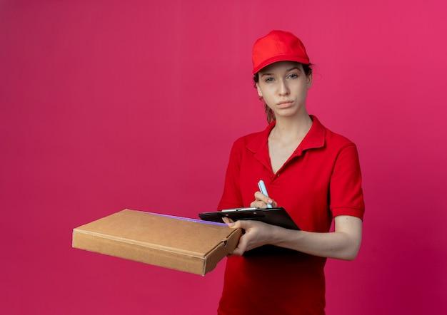 Zelfverzekerd jong mooi bezorgmeisje in rood uniform en pet met pizzapakketpen en klembord geïsoleerd op karmozijnrode achtergrond
