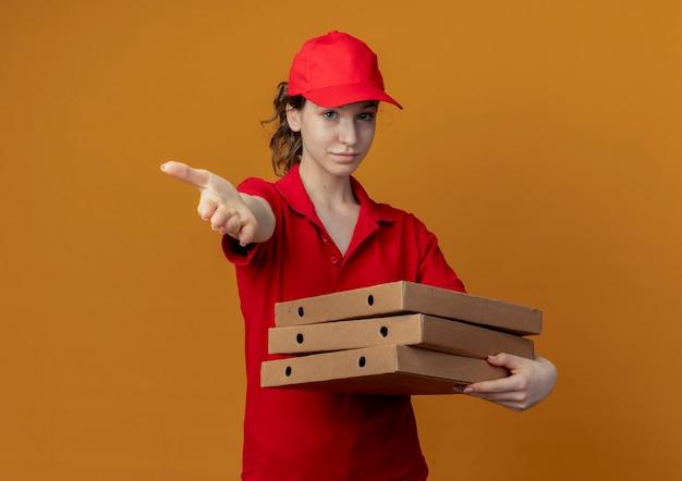 Zelfverzekerd jong, mooi bezorgmeisje in rood uniform en pet met pizzapakketten en hand uitstrekkend naar camera