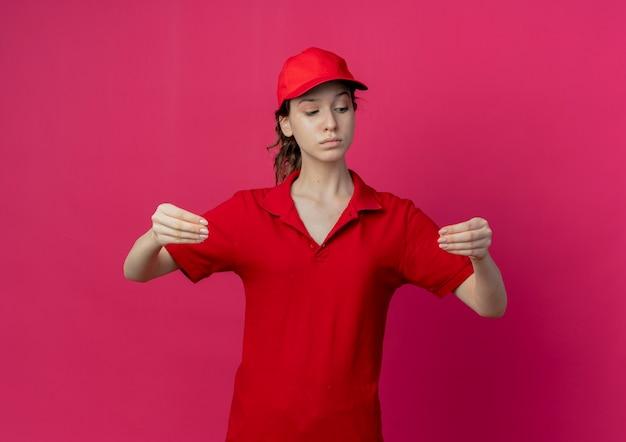 Zelfverzekerd jong mooi bezorgmeisje in rood uniform en pet neerkijkt alsof je iets vasthoudt dat op een karmozijnrode achtergrond wordt geïsoleerd