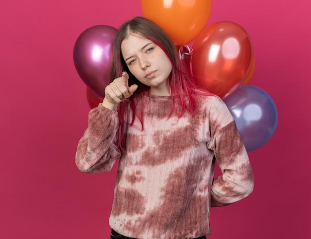Zelfverzekerd jong mooi meisje dat voor ballonnen staat en je een gebaar laat zien