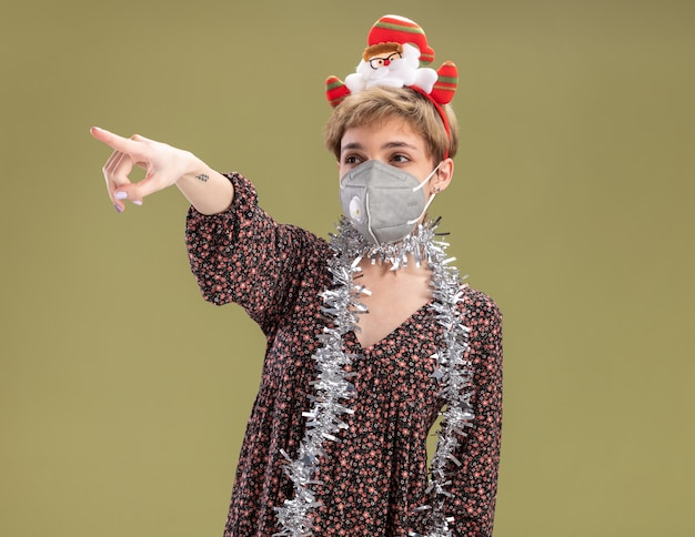 Zelfverzekerd jong mooi meisje dragen hoofdband van de kerstman en klatergoud slinger om nek met beschermend masker kijken en wijzend naar kant geïsoleerd op olijfgroene achtergrond met kopie ruimte