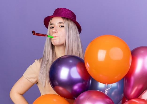 Zelfverzekerd jong mooi meisje met een feestmuts met ballonnen die een feestfluitje blazen dat op een blauwe muur wordt geïsoleerd
