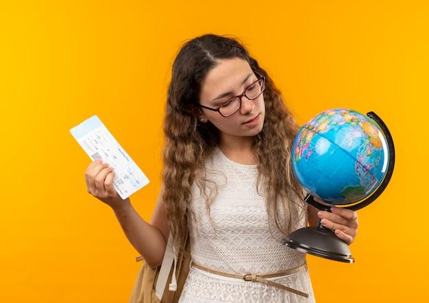 Zelfverzekerd jong mooi schoolmeisje die glazen en rugtas dragen die vliegtuigticket en bol bekijken die bol bekijken die op geel wordt geïsoleerd