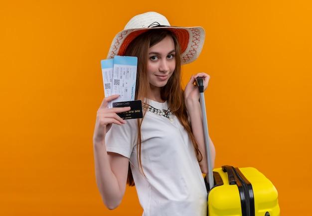 Zelfverzekerd jong reizigersmeisje die de vliegtuigkaartjes, de creditcard en de koffer van de hoedholding op geïsoleerde oranje ruimte met exemplaarruimte dragen