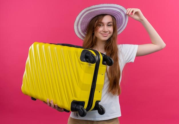 Zelfverzekerd jong reizigersmeisje die hoed dragen en koffer houden en hand op hoed zetten op geïsoleerde roze ruimte