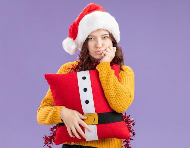 Zelfverzekerd jong slavisch meisje met kerstmuts en met slinger om nek legt hand op kin en houdt versierd kussen geïsoleerd op paarse muur met kopieerruimte