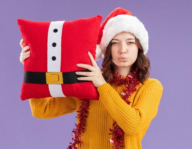 Zelfverzekerd jong slavisch meisje met kerstmuts en met slinger om nek met versierd kussen geïsoleerd op paarse achtergrond met kopie ruimte