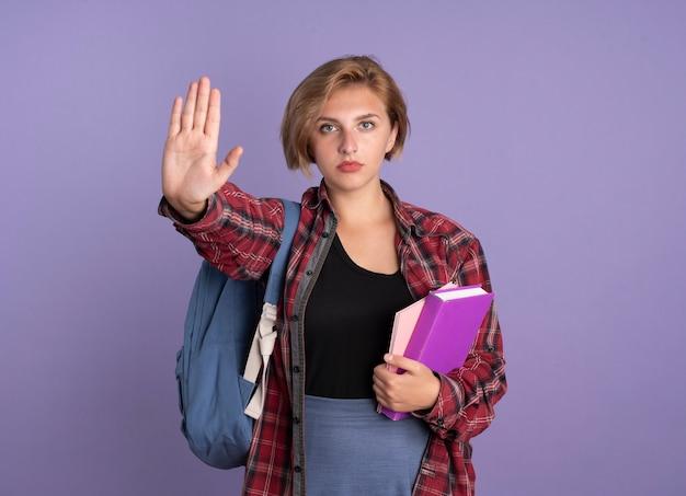 Zelfverzekerd jong slavisch studentenmeisje dat rugzak draagt, houdt boek- en notitieboekjegebaren stop handteken