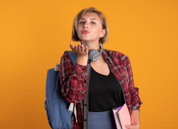 Zelfverzekerd jong slavisch studentenmeisje met koptelefoon met rugzak stuurt kus met hand