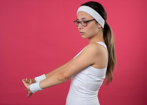 Zelfverzekerd jong sportief meisje met een optische bril met een hoofdband en polsbandjes staat zijwaarts hand in hand