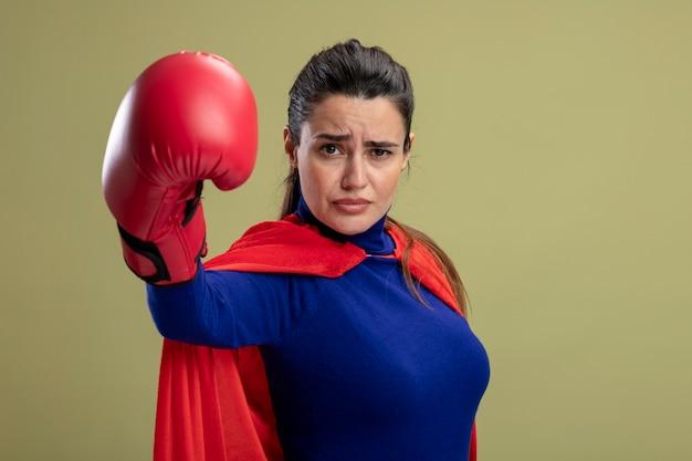 Zelfverzekerd jong superheld meisje bokshandschoenen dragen die hand stak op camera geïsoleerd op olijfgroene achtergrond