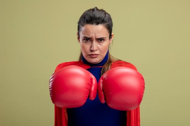 Zelfverzekerd jong superheld meisje bokshandschoenen dragen die handen stak op camera geïsoleerd op olijfgroene achtergrond