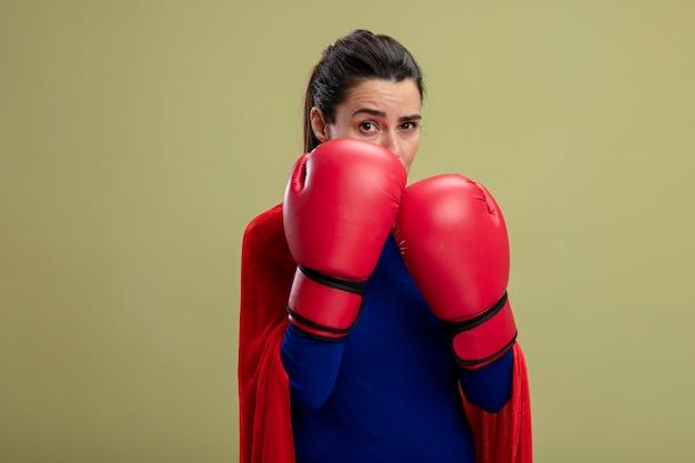 Zelfverzekerd jong superheld meisje bokshandschoenen dragen staande in de strijd pose geïsoleerd op olijfgroen