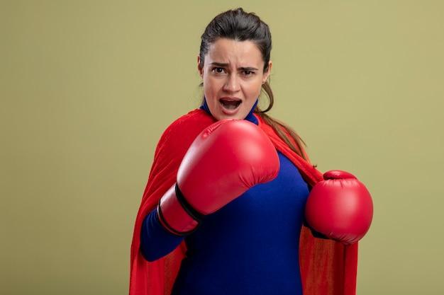 Zelfverzekerd jong superheld meisje bokshandschoenen dragen staande in de strijd pose geïsoleerd op olijfgroene achtergrond