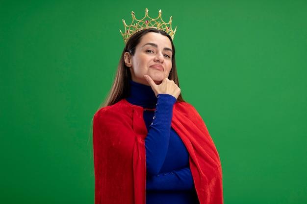 Zelfverzekerd jong superheld meisje dragen kroon pakte kin geïsoleerd op groene achtergrond