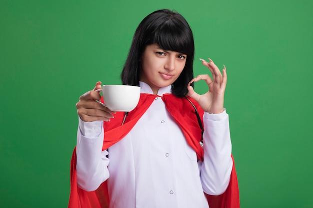 Zelfverzekerd jong superheld meisje dragen stethoscoop met medische mantel en mantel houden kopje thee weergegeven: ok gebaar geïsoleerd op groen