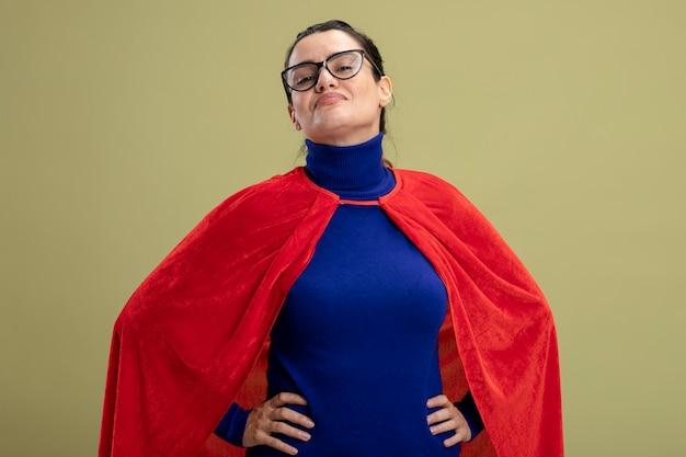 Zelfverzekerd jong superheld meisje met bril handen op heup geïsoleerd op olijfgroen