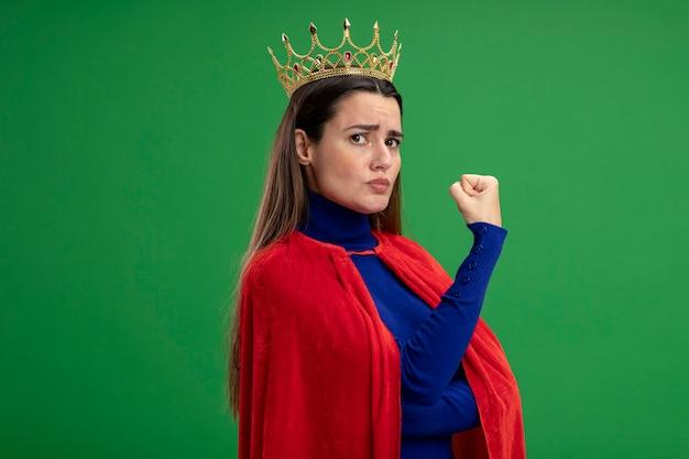 Zelfverzekerd jong superheldenmeisje die kroon dragen die sterk gebaar tonen dat op groene achtergrond wordt geïsoleerd