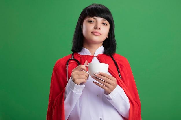 Zelfverzekerd jong superheldenmeisje die stethoscoop met medisch gewaad en mantel dragen die kopje thee houden geïsoleerd op groene muur