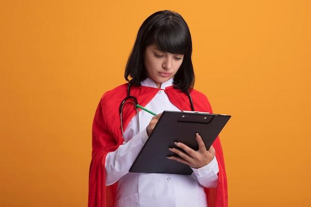 Zelfverzekerd jong superheldmeisje dat een stethoscoop met een medisch kleed en een mantel draagt die iets op het klembord schrijft