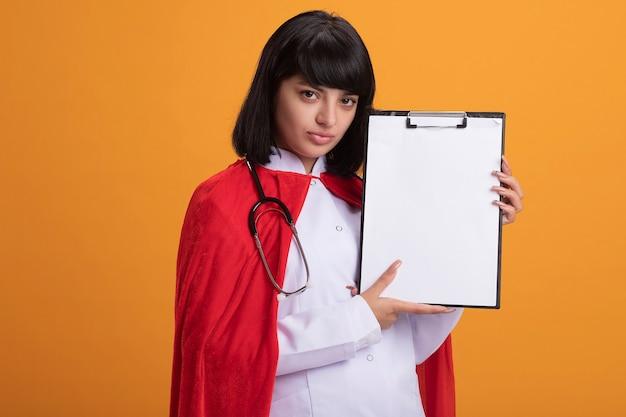 Zelfverzekerd jong superheldmeisje dat stethoscoop met medisch kleed en klembord van de mantelholding draagt