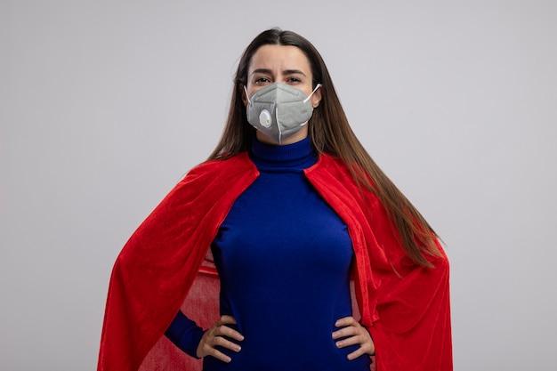 Zelfverzekerd jong superheldmeisje die medische masker dragen die handen op heup zetten die op witte achtergrond wordt geïsoleerd
