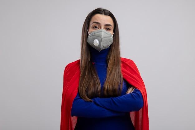 Zelfverzekerd jong superheromeisje die medisch masker dragen die handen kruisen die op wit worden geïsoleerd