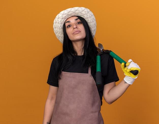 Zelfverzekerd jong tuinmanmeisje met uniform en hoed met tuinmanhandschoenen met heggenschaar op schouder kijkend naar voorkant geïsoleerd op oranje muur met kopieerruimte