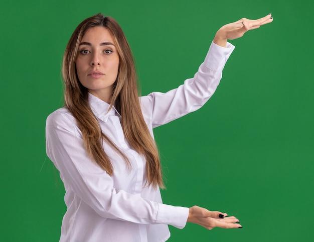 Zelfverzekerd jong vrij kaukasisch meisje beweert iets op groen vast te houden