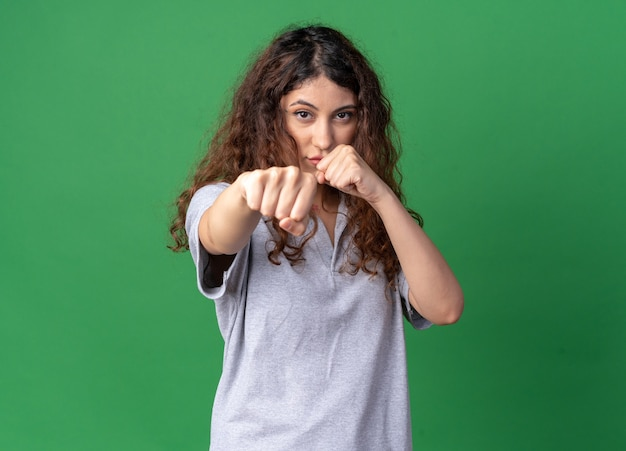 Zelfverzekerd jong, vrij kaukasisch meisje dat boksgebaar doet geïsoleerd op een groene muur met kopieerruimte