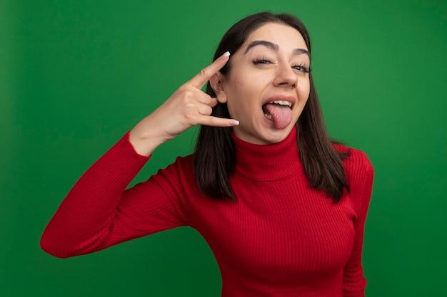 Zelfverzekerd jong, vrij kaukasisch meisje dat hand in de buurt van het hoofd houdt en een rotsbord doet met tong geïsoleerd op een groene muur