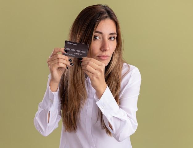 Zelfverzekerd jong, vrij kaukasisch meisje heeft een creditcard