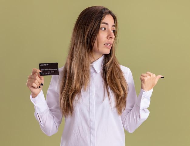 Zelfverzekerd jong, vrij kaukasisch meisje houdt een creditcard vast die naar de zijkant kijkt en wijst