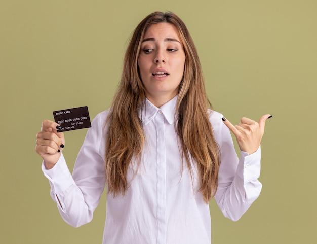 Zelfverzekerd jong, vrij kaukasisch meisje houdt en kijkt naar creditcard terwijl ze een los gebaar doet dat op een olijfgroene muur is geïsoleerd met kopieerruimte