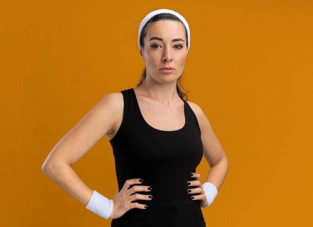 Zelfverzekerd jong vrij sportief meisje met hoofdband en polsbandjes die de handen op de taille houden