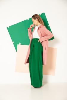 Zelfverzekerd jong vrouwelijk model in een elegante pastelroze jas en een felgroene broek die de lentemode vertegenwoordigt en wegkijkt in de studio
