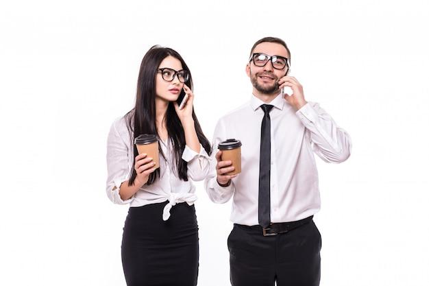 Zelfverzekerd jong zakenpaar staande houden kopjes afhaalkoffie, met behulp van mobiele telefoons, praten geïsoleerd op witte achtergrond,