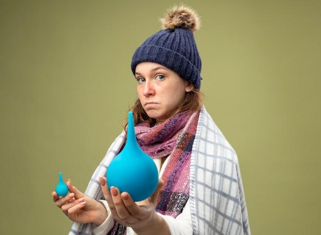 Zelfverzekerd jong ziek meisje dragen witte mantel en winter hoed met sjaal verpakt in plaid bedrijf klysma's geïsoleerd op olijfgroen