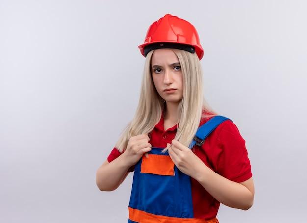 Zelfverzekerd jonge blonde ingenieur bouwer meisje in uniform handen op haar uniform op geïsoleerde witte ruimte met kopie ruimte te zetten Gratis Foto