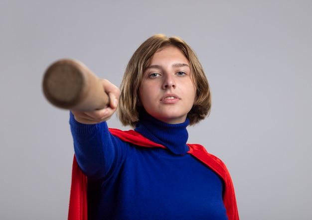 Zelfverzekerd jonge blonde superheld meisje in rode cape honkbalknuppel uitrekken naar camera kijken camera geïsoleerd op een witte achtergrond met kopie ruimte