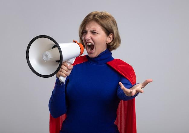 Zelfverzekerd jonge blonde superheld meisje in rode cape schreeuwen in luidspreker met lege hand kijken naar kant geïsoleerd op een witte achtergrond